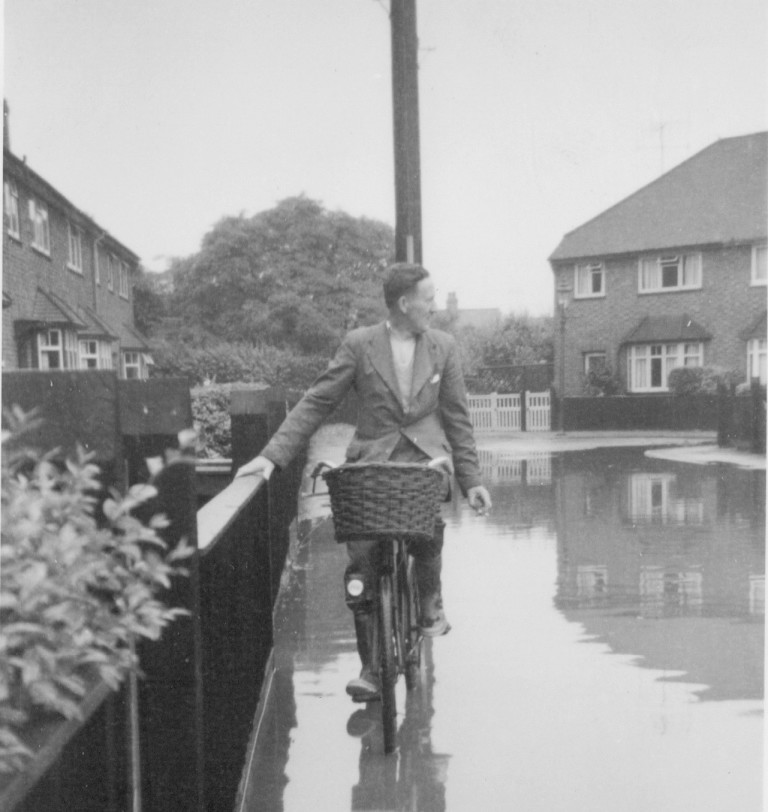 Flash flood in Natal Road - Gordon Fakes takes his bike through the flood water in June 1959. Family home at 58 in the background.